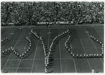 WVU Marching band in formation to spell 'WVU' on the field.