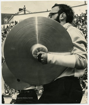 A cymbalist performs with the band on the field.