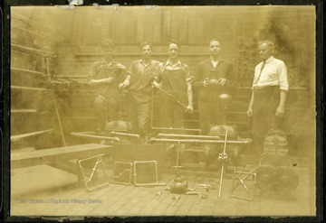 Students of pipe fitting class of 1927 pose in Mechanical Hall with Rufus West on far right.