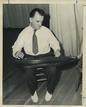 'Patrick Gainer, noted authority on folk culture, originator and master of ceremonies for the Glenville Folk Festival, plays 'Sugar in the Gourd,' a sprightly piece he heard frequently as a child. The instrument, a variation of the ancient rebec, was hand crafted for Gainer by a mountain friend.'
