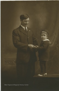 A portrait taken of a young child holding hands with his father.