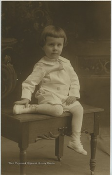 Portrait of a child sitting on a wooden bench.