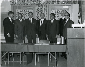 Gov. Smith (center) with a group of men standing around a conference table.