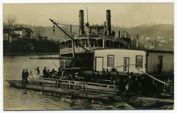 Postcard photograph of the steamboat 'Columbia' docking at the wharf on the Monongahela River at Morgantown next to a towboat and a ferry loaded with wagons, buggies and riders on horseback.