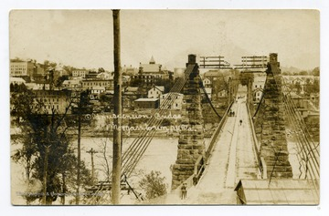 A view of the Old Suspension Bridge: pedestrians and a buggy going by.