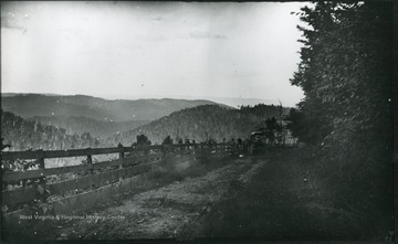 '51.W.23; Wed., July 16 after 6 P.M.' A landscape of a mountain range and a country road, with a carriage in the distance.