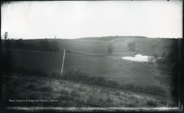 'Looking N. from a little sandy hill on right of pike and nearly alongside Dinkler's farm house seen in No 113. The place of the pike is shown by the telegraph wires through the road itself is low and hidden by the fringes of bushes. 110.D.66 I.C.; July 31, 1884, Thursday 3:50 pm, dark, cloudy'
