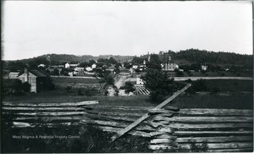 A photograph of a small town, possibly Harrisville, with a wooden fence in the foreground.