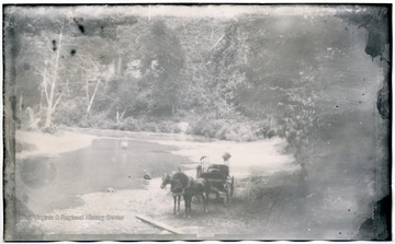11 W (5) Horse drawn carriage beside a river bed.