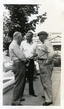 Photo from WVU College of Mineral Resources Scrapbook. Three unidentified men standing outside Clark Hall, WVU.