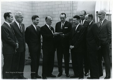 A group portrait of Paul Kent (far left), Butler (second from left), Harry Heflin (third from left), Robert Sloneger (second from right), Don Holland (third from right), and C.A. Arents (center).