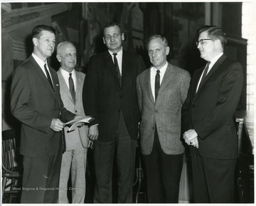Harry Heflin (far left) and President Paul Miller (second from right) standing with other individuals in White Hall.