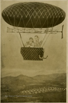 A blimp in the air with two males in a basket flies over a city view: a composite photo.