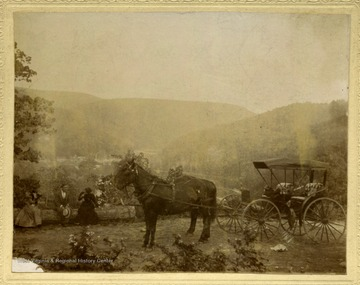 A Horse drawn carriage and passengers out in a scenic mountain view.