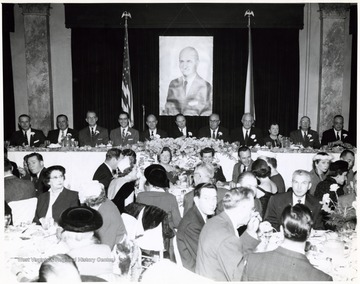 'Left to Right - (Speaker's Table); two unknown men, George Clinton (Parkersburg), Governor Cecil Underwood, Senator John D. Hoblitzell, Jr., Robert B. McDougle (Parkersburg), Leonard Hall, Senator Chapman Revercomb, three unknown.