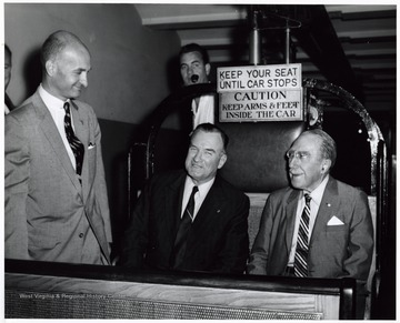 A photograph of Senator John D. Hoblitzell, Jr. (left) speaking with Senator Theodore Green (R.I.; seated right) and another man as they sit in an open cable car.