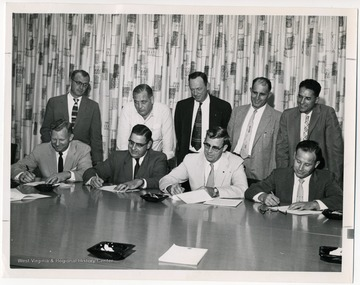 """Merger Agreement Signed- Culminating months of negotiations between W. Va State Federation of Labor (A.F.L) and the W. Va State Industrial Union Council (C.I.O), representatives of both groups formally sign an agreement on September 24, 1957 which paved the way for the merger convention on November 22, 1957. Shown (seated, left to right) are Benjamin W. Skeen, S.F.L secretary-treasurer; E. A. Carter, S.F.L president; Oscar L. Davis, I.U.C president and Miles C. Stanley, I.U.C secretary treasurer;(standing, left to right) Rene V. Zabeau and James Q. Papas, S.F.L vice-presidents; Rezin Hudkins, John Lambert and Charles Hess, I.U.C vice-presidents."""