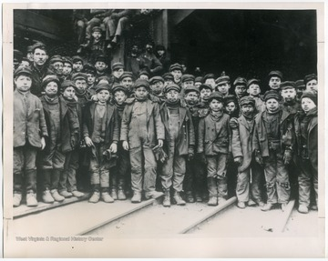 """No Time for School in 1911- Shown is a typical group of youngsters, aged nine to fourteen, at the end of a ten-hour shift in a W. Va coal mine in 1911. A day's wages averaged 50-75 cents. Known as 'breaker boys,' these children worked six days a week breaking up large chunks of coal, picking out slate and other impurities, and greasing coal cars. The A.F. of L. fought for passage of effective child labor laws to prohibit such exploitation of youthful workers in many mines, mills and factories."""