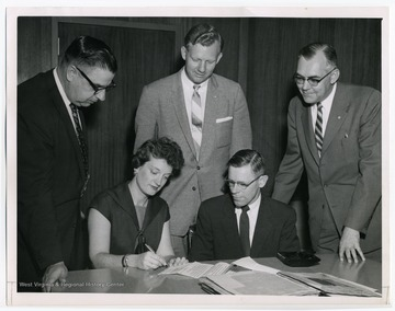 """Evelyn L. K. Harris and Frank J. Krebs are shown in April, 1958 signing a contract for preparation of manuscript for the book, 'From Humble Beginnings, W. Va State Federation of Labor, 1903-1957.' E. A. Carter, Benjamin W. Skeen and Glen Armstrong (standing, left to right), members of the Trustees and Editorial Board of the W. Va Labor History Publishing Fund, look on."""