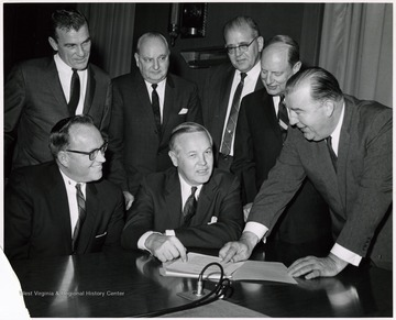 A photograph of Senator Randolph (far right) gathered with Governor Smith (seated, center) and others.