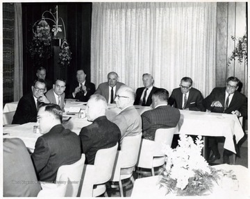 A photograph of a gathering of West Virginia politicians. Herman Walker (far table, right), Governor Hulett C. Smith (far table, third from right), Dyke Raese (far table, third from left), Jennings Randolph (far table, second from left), Paul Miller (far table, left), Howard Smyth (foreground, second from left), Elmer Prince (foreground, third from left).