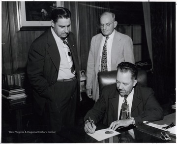 A photograph of Governor Patteson (seated) signing a piece of paper, with Eugene Carter (left), President of the West Virginia Federation of Labor, and another man standing behind him.