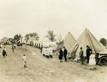 A photograph of people standing outside a long row of tents at a campground. Print number 1066.