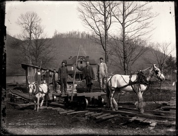 Loggers on horse drawn train carts.