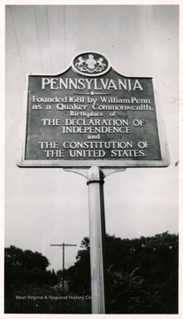 A Pennsylvania highway marker stands between Wheeling, W. Va. and Washington, PA on the US Route 40.  The marker reads: Pennsylvania--founded 1681 by William Penn ans a Quaker Commonwealth, Birthplace of the Declaration of Independence and the Constitution of the United States.