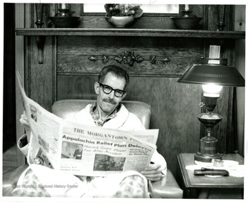 An unidentified man sits in couch with papers in his hands.