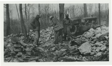 Three men surrounded by stone working. The names Jex and Bill appear on the back of photo.