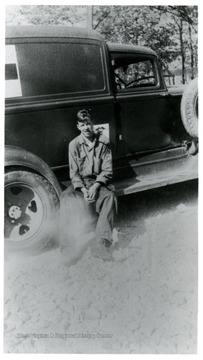 A portrait of Crane Weaver sitting on a footstep of truck; CCC 32.