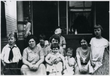 ' Far L- John (Jack) Nanz, Far R- Betty Nanz, Woman holding child: Mary H. Coleman Donahue, child Mary Dorothy Blume, child 3rd from R-Ruth Nanz,and woman with face scratched out Agnes Coleman Nanz.'