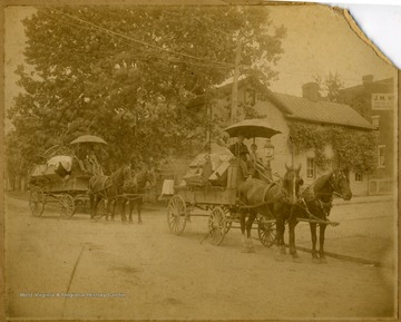 "' ""Wood's house"" of two horse drawn wagons, each pulling a man, a boy and furniture on Pleasant Street and University Ave in Morgantown, W. Va."