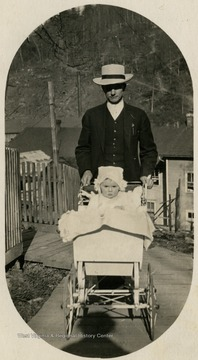 'Dr. Ladwig and his daughter, Cornelia. Dr Ladwig is pushing the pram, something few men did then, especially in a lumber or mining town. This say something about the man.'