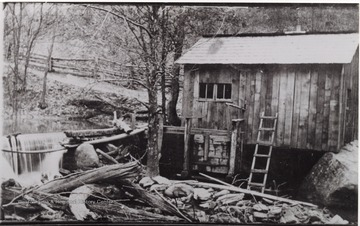 Picture of a wooden building next to the Birch River.