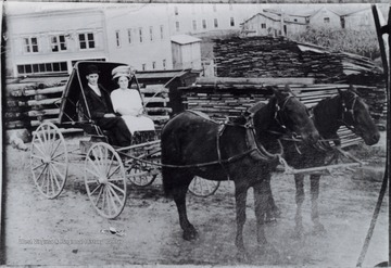 Portrait of Lula Rose and a man on a carriage behind the Lemley Mills building and the Central Hotel.