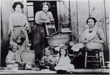 Women and children in the middle of with various household chores such as laundry, and filling kerosene lanterns. The structure is believed to be a boarding house near Hacker Valley, W. Va.