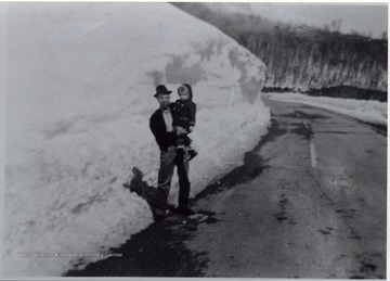 Father and son standing next to a large snow bank.