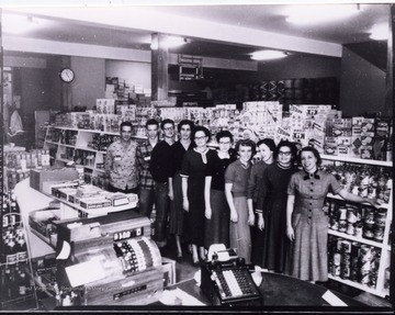 Portrait of workers in front of shelves of groceries.