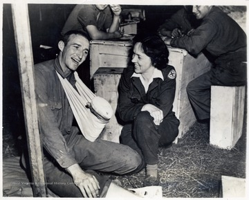 Cornelia Ladwig, Red Cross recreational director of Clarksburg, W. Va. keeps Pfc. Burton Crawford, left, of Elkins, W. Va. amused. He is one of the many recuperating patients in an evacuation hospital, somewhere in France.