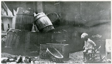 Back yard of house on Sturgiss Avenue with unidentified child in rocker and large pile of barrels.
