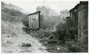 "The ""dry closet"" is erected over an open water course. Framed building on the right is a street car barn."