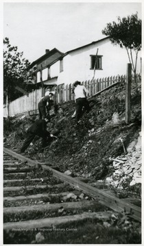 Unidentified men building a new fence around South Sabraton dwellings on Sturgiss Street.