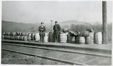 A collection of liquor containers along a track with two unidentified men holding bottles.