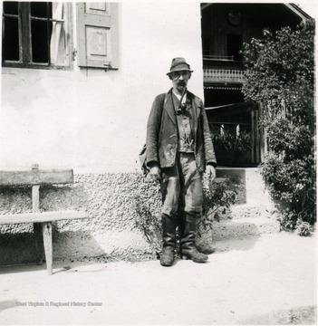 Unidentified man dressed in laborer's clothes, including sturdy boots. This photograph was taken approximately three months after Germany surrendered. Note the unusual pipe the man has in his mouth.