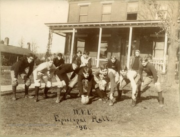 Students in football uniforms pose in offensive set in front of Episcopal Hall.