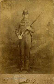 A cabinet card portrait of a young man in full military uniform, holding a weapon.