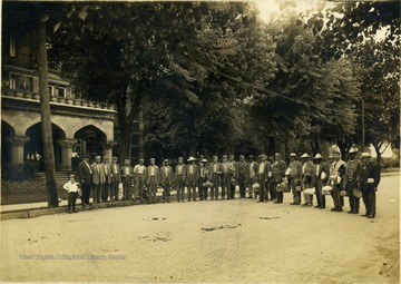 Group portrait of several unidentified inmates standing on a brick paved street on the state prison grounds. Two men standing at each end, wearing suits, are probably staff. None of the subjects are identified.