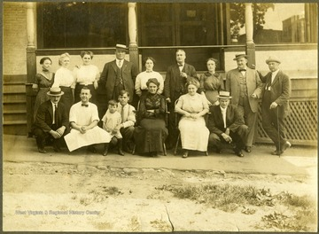 "Inscribed on back: ""Believed to be early hotel (on the corner of 5th Avenue and Front = conjecture) in Hinton. Possibly Rudisell 2nd from L, standing [All other persons are unidentified]. Hotel staff is posed in front of the entrance steps,leading to a wide wrap-around porch with double door entrance.Tall multi-story masonry bldgs appear in R beyond porch. Purchased by Stephen Trail in Hinton West Virginia."""